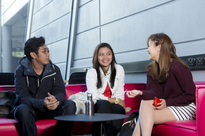 three students, two girls and a boy, sitting together on a red couch, talking.