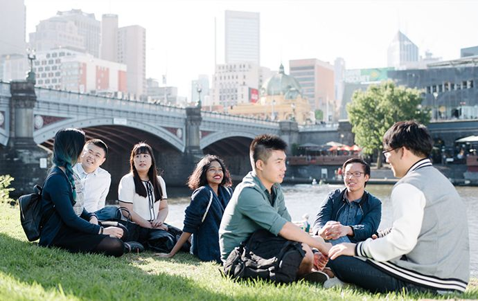 Students sit on the banks of the Yarra River with Melbourne Skyline in the background