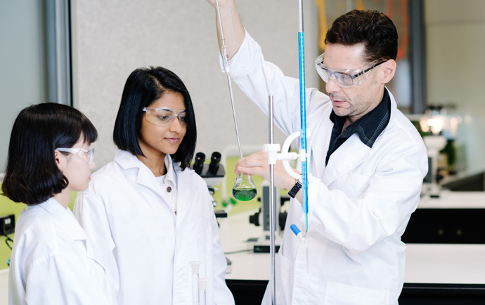 Teacher demonstrating experiment to 2 students in a lab