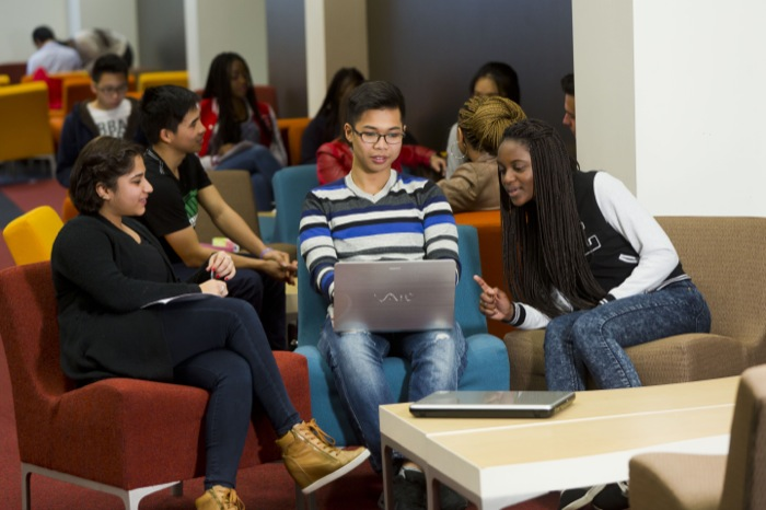 Multicultural group of students sitting on colourful couches looking at a laptop.