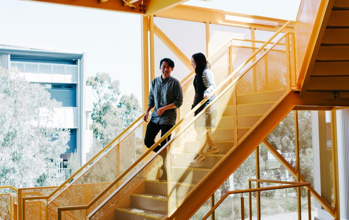2 Students walking down the stairs in Learning Village