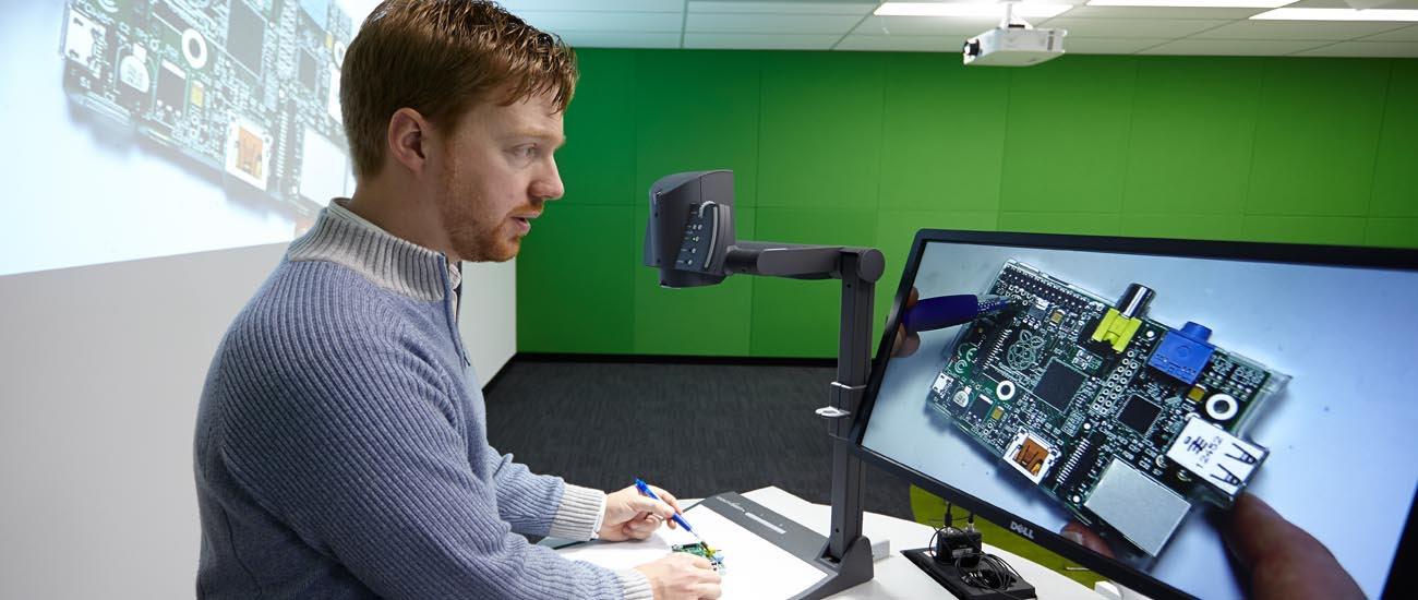 IT teacher demonstrating with PC motherboard