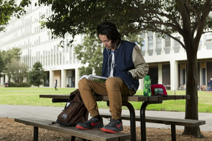 Male student sitting on a table in front of the Menzies building, with his feet on the seat reading a text book and listening to music