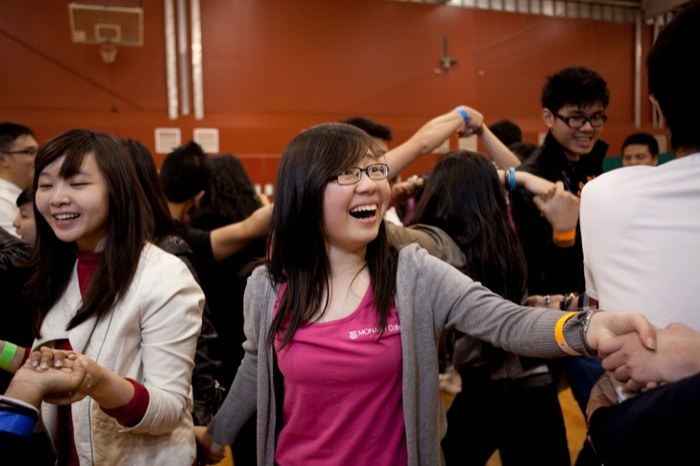 A group of students holding hands while participating in an orientation game. Students are smiling and laughing.