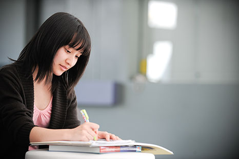 Student sitting at a table writing in a text book.