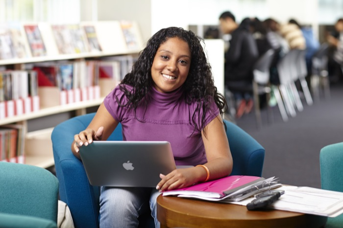 girl in purple jumper sitting in library with laptop