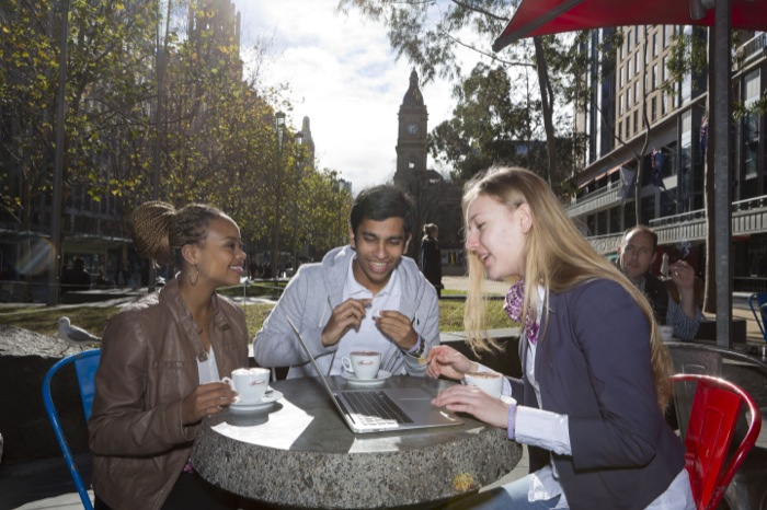 Monash College students, two females and male, sitting at a café in Melbourne on a sunny day with a laptop and coffee.