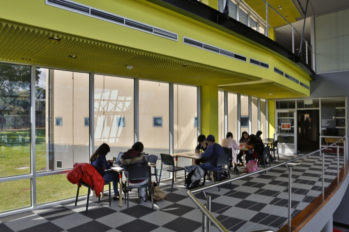 10 students studying in small groups inside the Monash College building with a large window looking on to the lawn, and yellow roof.