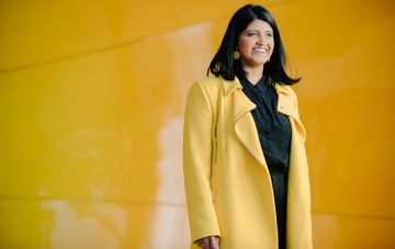 Student in yellow coat smiling infront of yellow wall