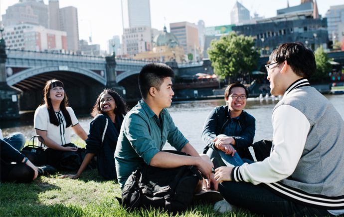 Group Students sitting along the Yarra River bank