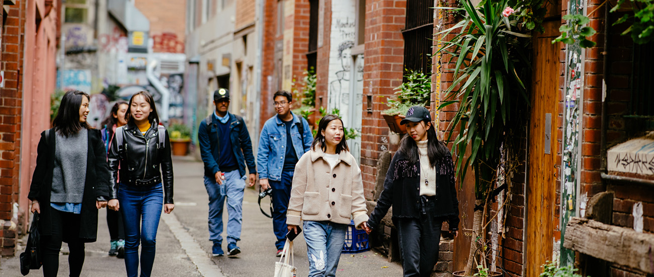 Group of students walking through Melbourne City alley