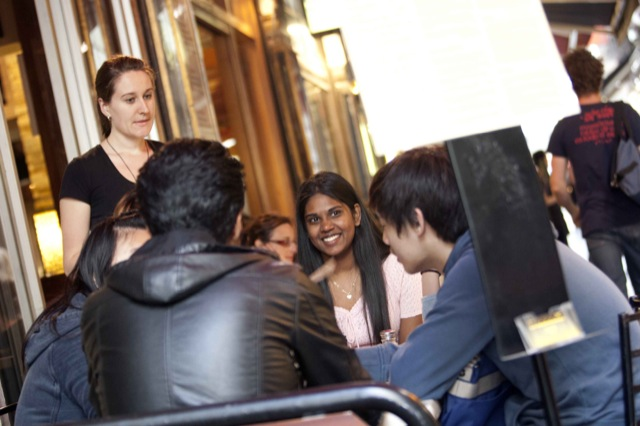 group of students sitting at an outside café drinking coffee