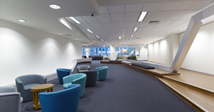 Entrance of the Monash College Melbourne City campus with blue couches, wooden floorboards and interesting lights.