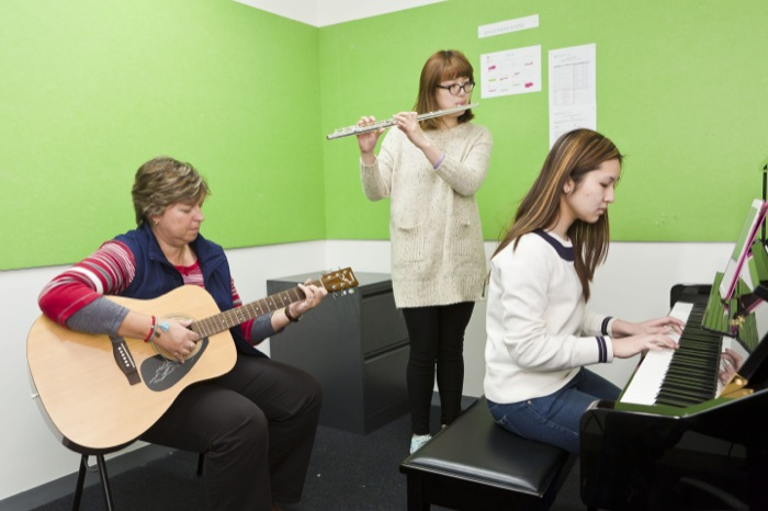 Two female students playing the piano and flute in a music practise room with a female teacher playing guitar.