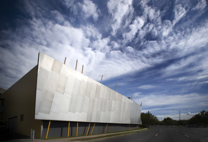 Large square Monash Art Design and Architecture building with bright blue sky and soft fluffy clouds.