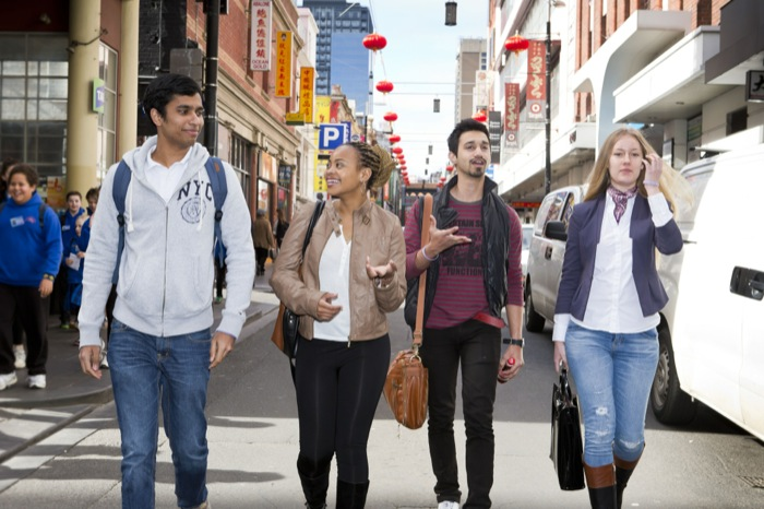 four happy students from different countries walking together down a busy Melbourne street