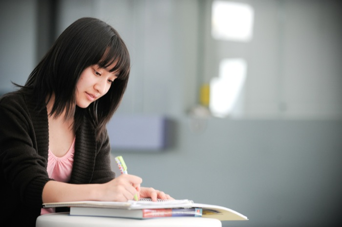Female student sitting at desk writing in a book