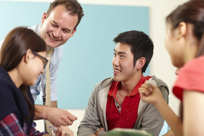 Male teacher in a classroom talking with two female and one male student.