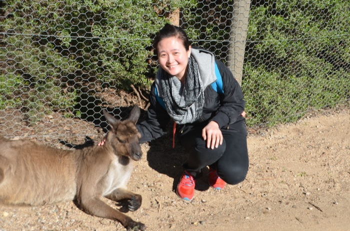 A female student on a day trip to the zoo posing with a kangaroo that is lying in the sun.