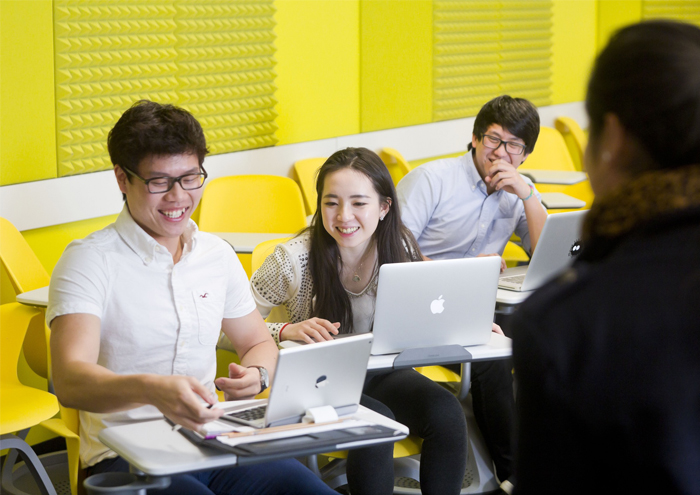 Three students sitting in yellow classroom with laptops
