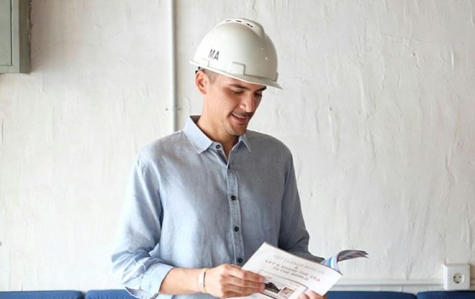 Grad-Testimonials-IT-grad-Mahdi-Grad in hard hat looking at paperwork 2